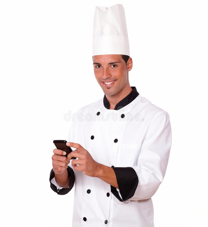 Cocinero hispánico encantador que envía un mensaje foto de archivo libre de regalías