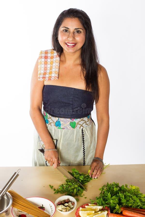 Cocinero indio sonriente Cuts Herbs foto de archivo