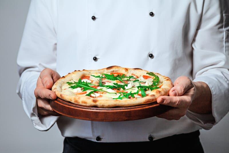 Cocinero italiano del cocinero del hombre que sostiene una pizza acabada en un fondo gris foto de archivo