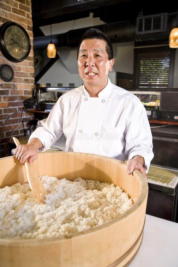 Cocinero japonés que prepara el arroz para el sushi fotografía de archivo
