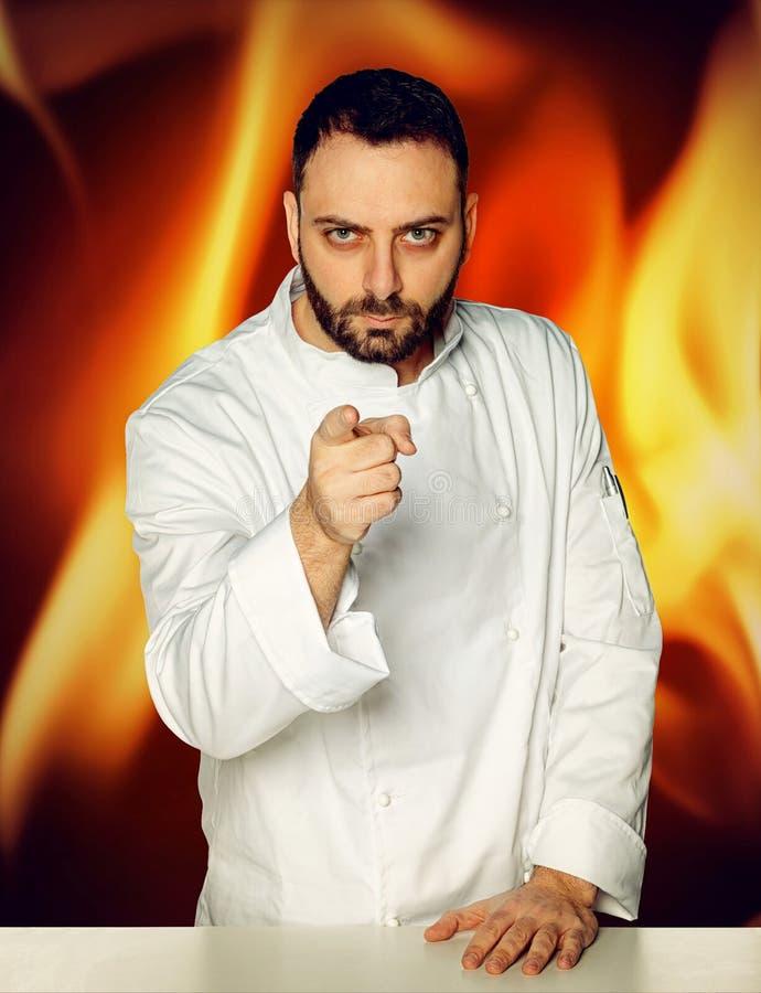 Cocinero joven en fondo ardiente imagen de archivo
