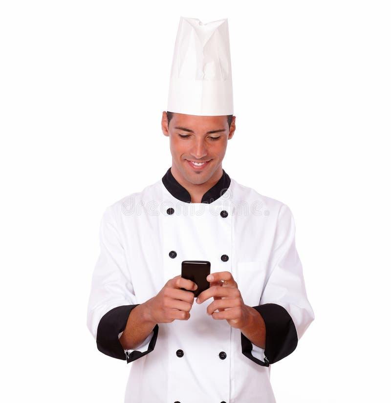 Cocinero joven profesional que manda un SMS a un mensaje fotos de archivo
