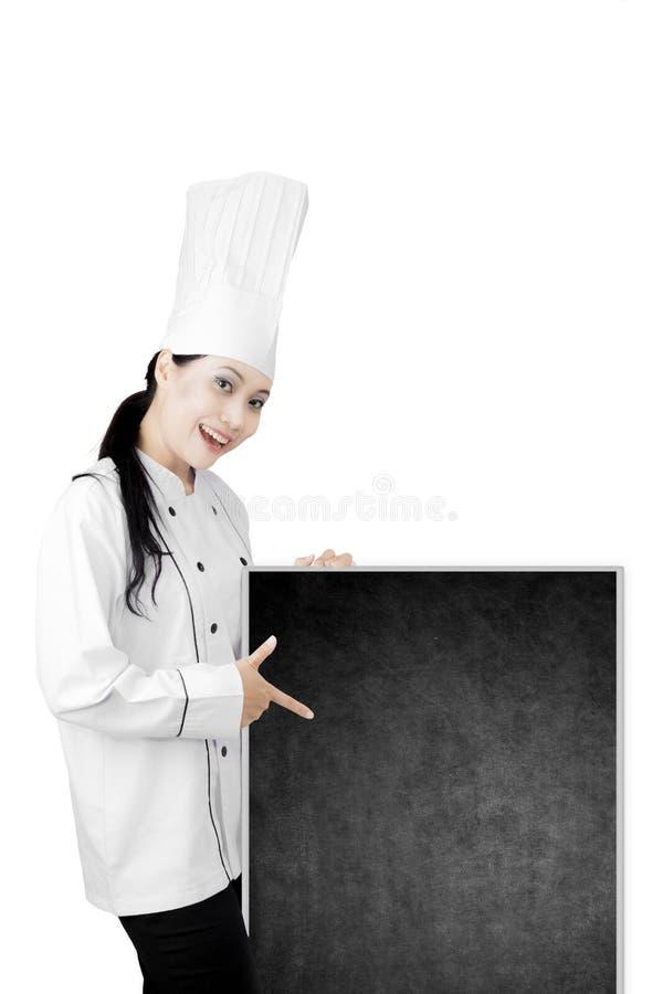 Cocinero joven que muestra una pizarra vacía fotografía de archivo libre de regalías