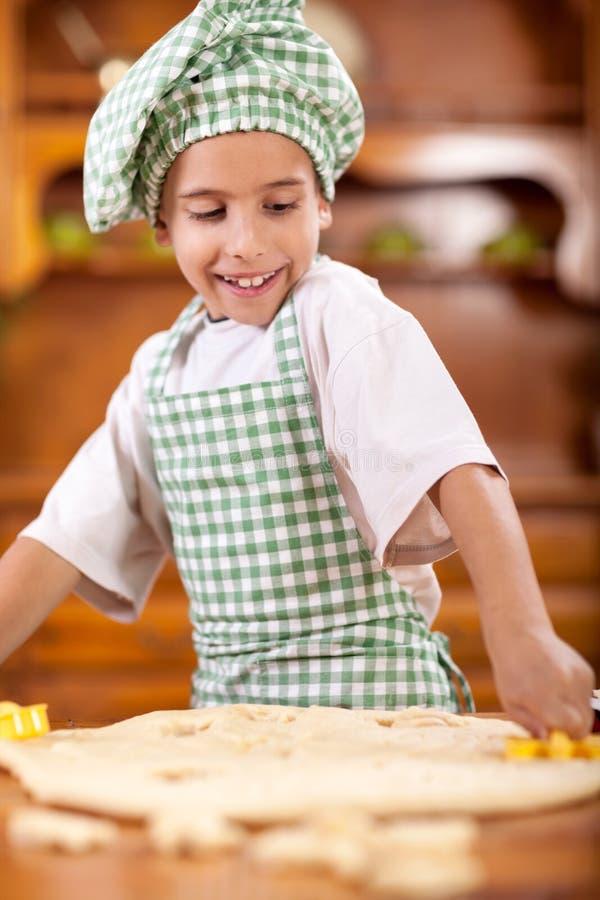 Cocinero joven sonriente feliz del muchacho en la cocina que hace la pasta foto de archivo