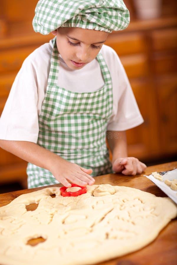Cocinero joven sonriente feliz del muchacho en la cocina que hace la pasta fotografía de archivo libre de regalías
