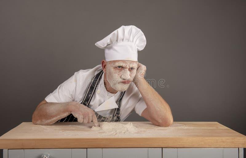 Cocinero maduro cubierto en la harina que parece molestada y alimentada para arriba foto de archivo