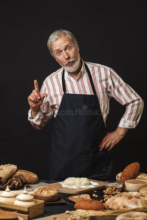 Cocinero mayor de sexo masculino aislado en fondo negro fotos de archivo