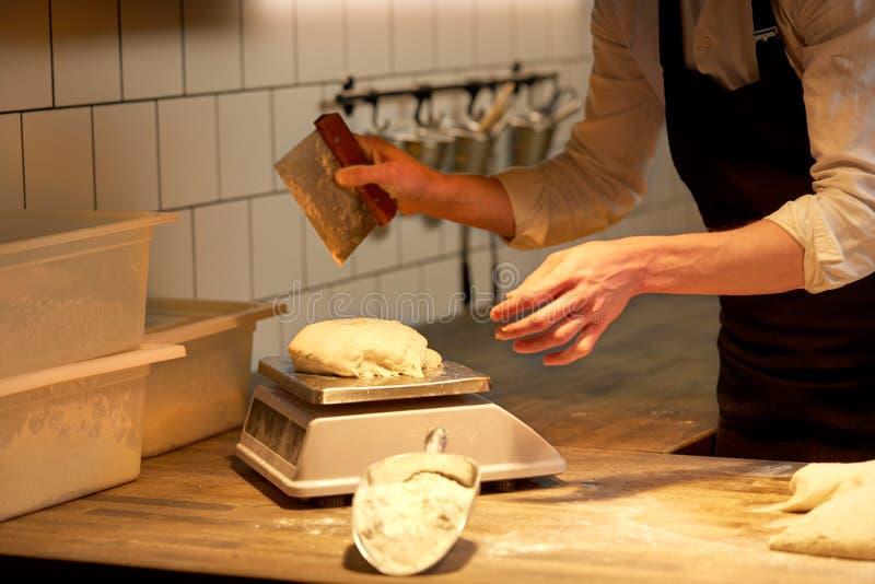 Cocinero o panadero que pesa la pasta en escala en la panadería imagen de archivo libre de regalías