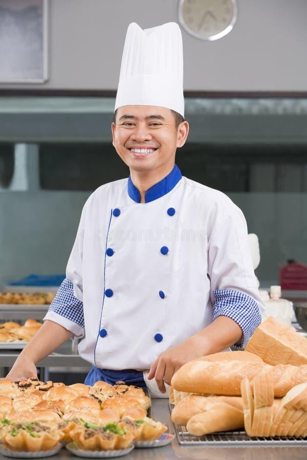 Cocinero o panadero que presenta delante de los pasteles imagenes de archivo