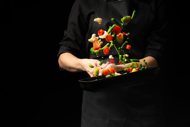 Cocinero profesional Él prepara un plato con las verduras en un cazo en fondo negro, menú, libro de la receta, comida sana imágenes de archivo libres de regalías