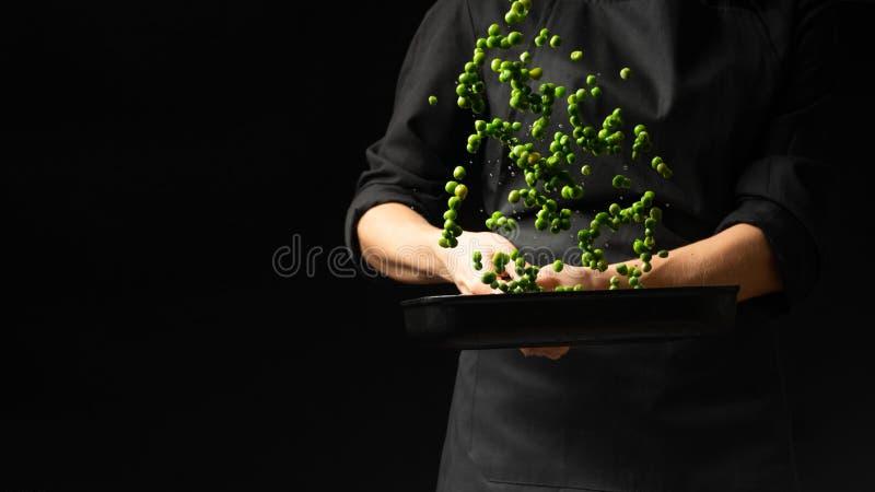 Cocinero profesional cocinero que prepara el plato con los guisantes verdes en una cacerola En un fondo negro menú, libro de la r imágenes de archivo libres de regalías