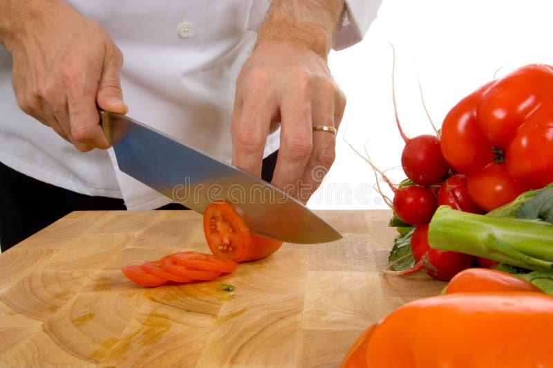 Cocinero profesional que rebana el tomate fotos de archivo libres de regalías