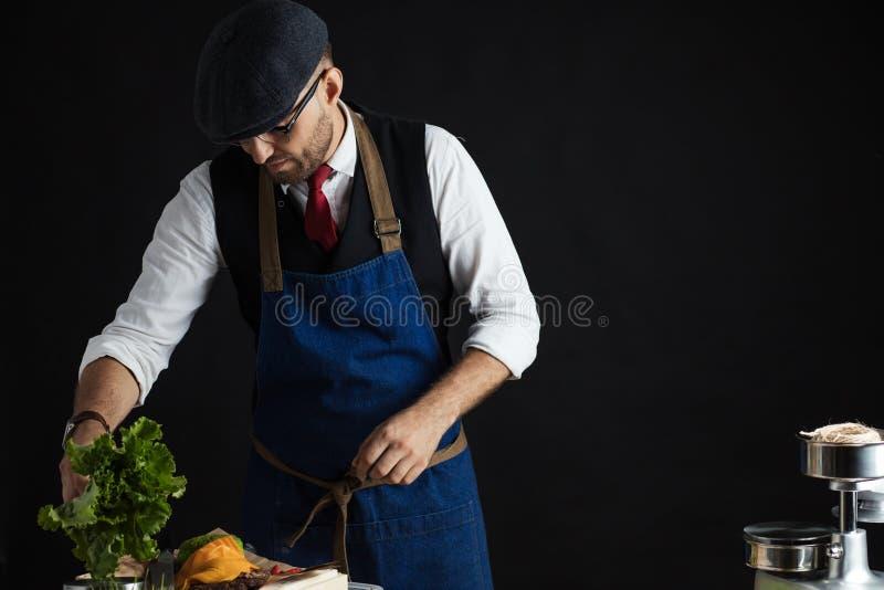 Cocinero que añade lechuga en la hamburguesa Preparación de la hamburguesa fotos de archivo libres de regalías