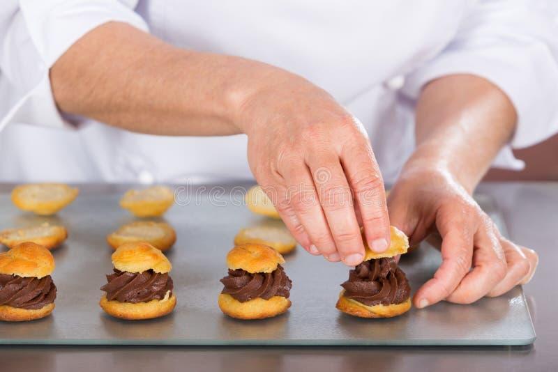 Cocinero que adorna algunos profiteroles foto de archivo