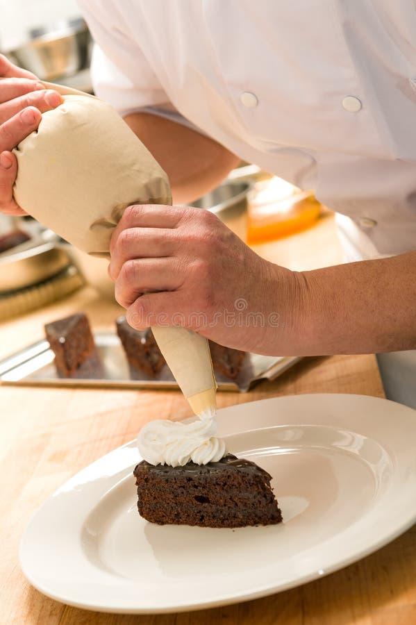Cocinero que adorna la torta con crema azotada imagenes de archivo