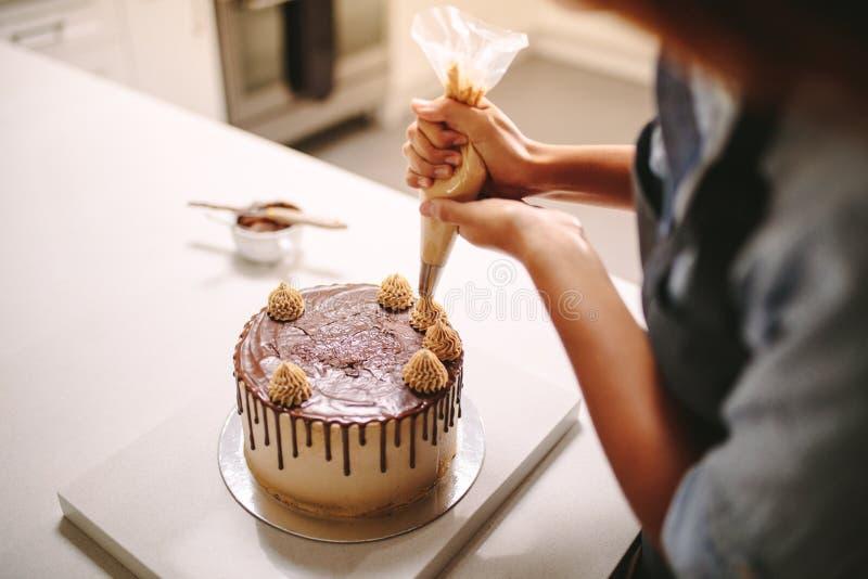 Cocinero que adorna la torta con crema imagen de archivo
