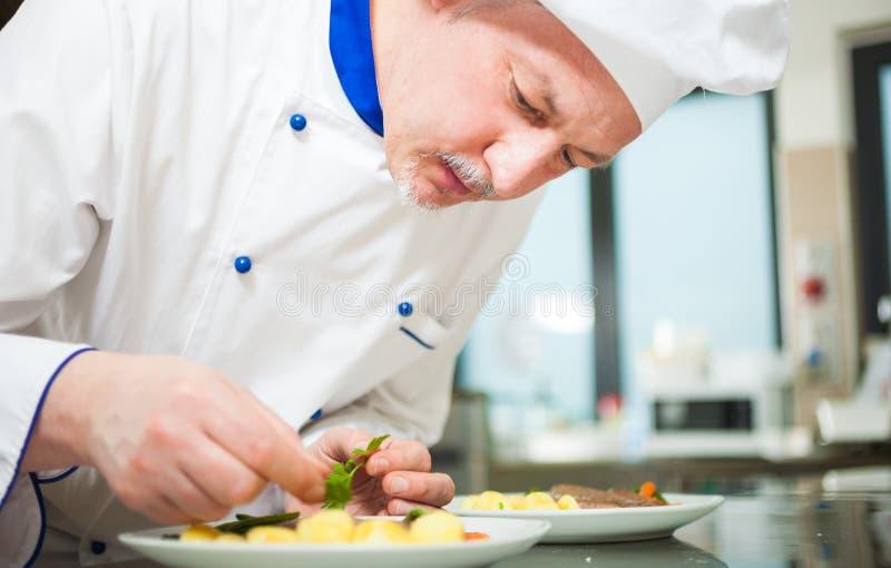 Cocinero que adorna un plato foto de archivo libre de regalías