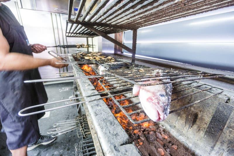 Cocinero que asa a la parrilla pescados de oro deliciosos en el carbón de leña imagenes de archivo