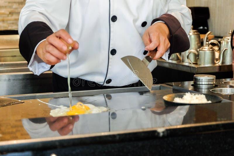Cocinero que cocina con el huevo en la cocina imagen de archivo