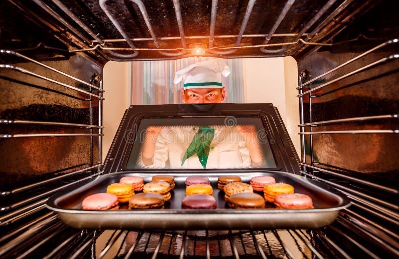 Cocinero que cocina en el horno foto de archivo