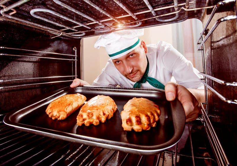 Cocinero que cocina en el horno fotos de archivo