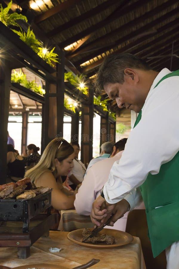 Cocinero que cocina la carne en el restaurante de LA CASA DEL CAMBA foto de archivo