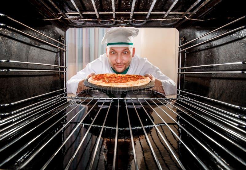 Cocinero que cocina la pizza en el horno foto de archivo