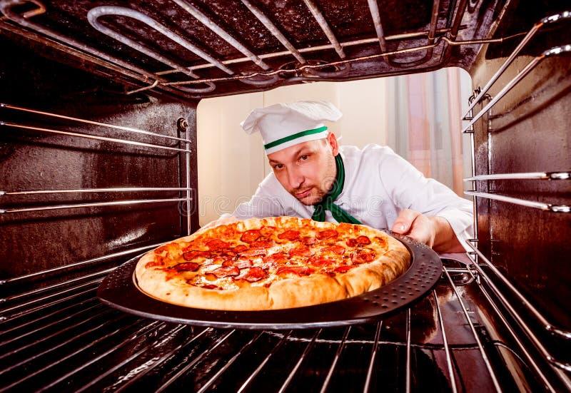Cocinero que cocina la pizza en el horno fotografía de archivo