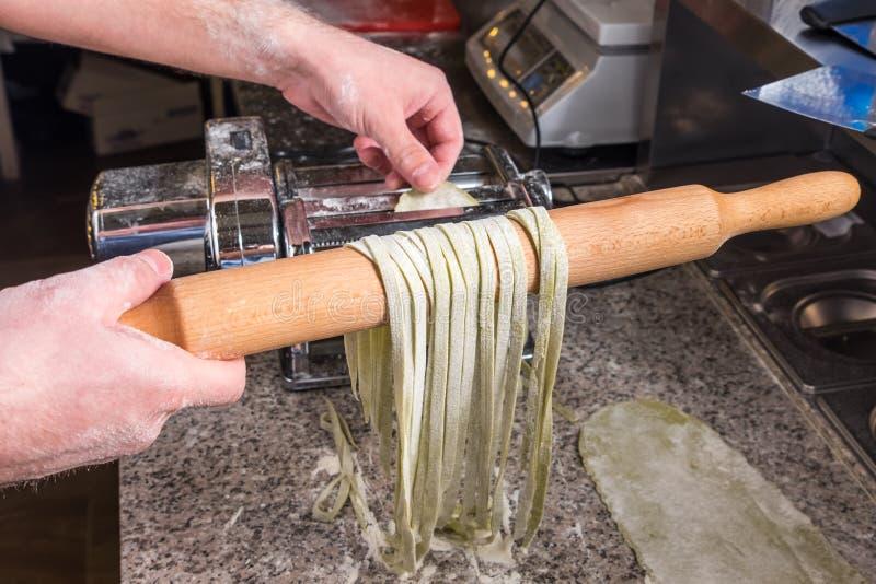 Cocinero que cocina los espaguetis italianos en el restaurante fotos de archivo libres de regalías