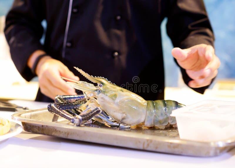 Cocinero que cocina los mariscos, mano que corta la gamba negra cruda del tigre imágenes de archivo libres de regalías