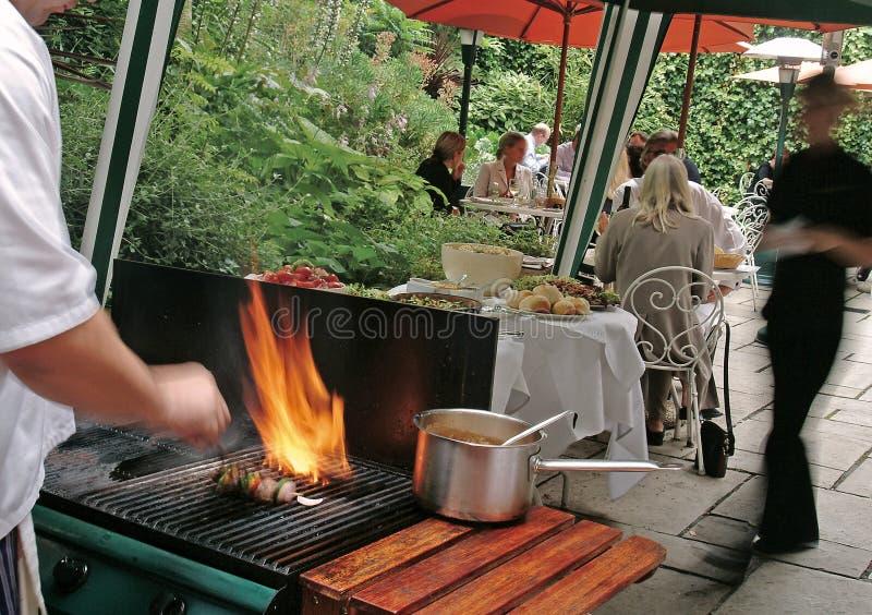Cocinero que cocina un Bbq en el pub foto de archivo