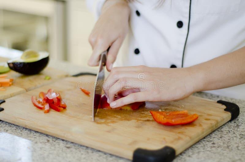 Cocinero que corta algunas verduras imagen de archivo