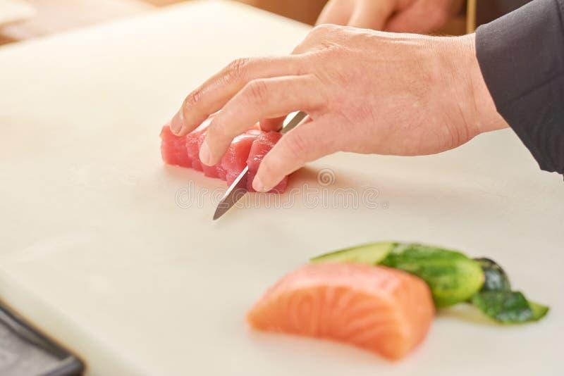 Cocinero que corta el atún fresco en pequeños pedazos foto de archivo