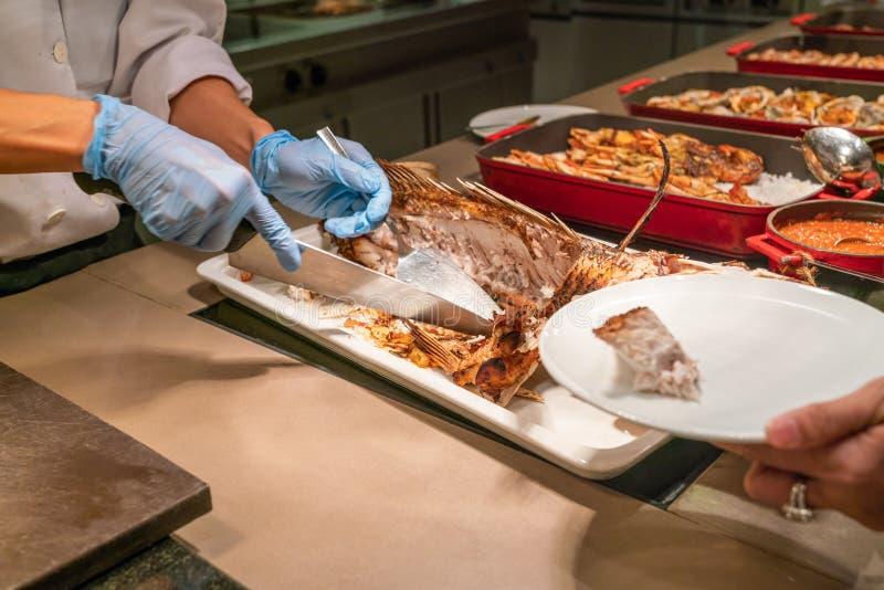 Cocinero que corta y que corta pescados asados a la parrilla imagenes de archivo