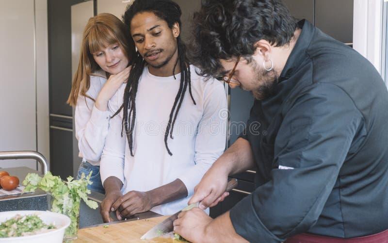 Cocinero que enseña un par multirracial a cómo hacer una comida fotografía de archivo libre de regalías