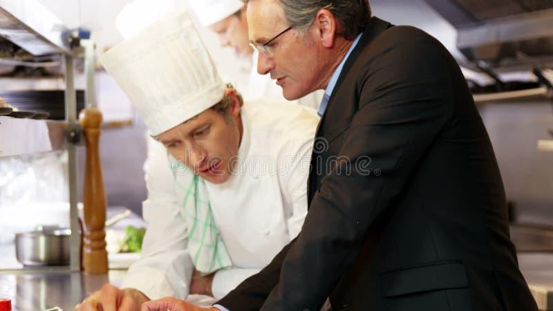 Cocinero que habla con el patrón almacen de metraje de vídeo