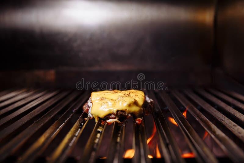 Cocinero que hace la hamburguesa Cocinar la hamburguesa Chuleta de la carne de vaca o del cerdo con el queso que asa a la parrill fotografía de archivo