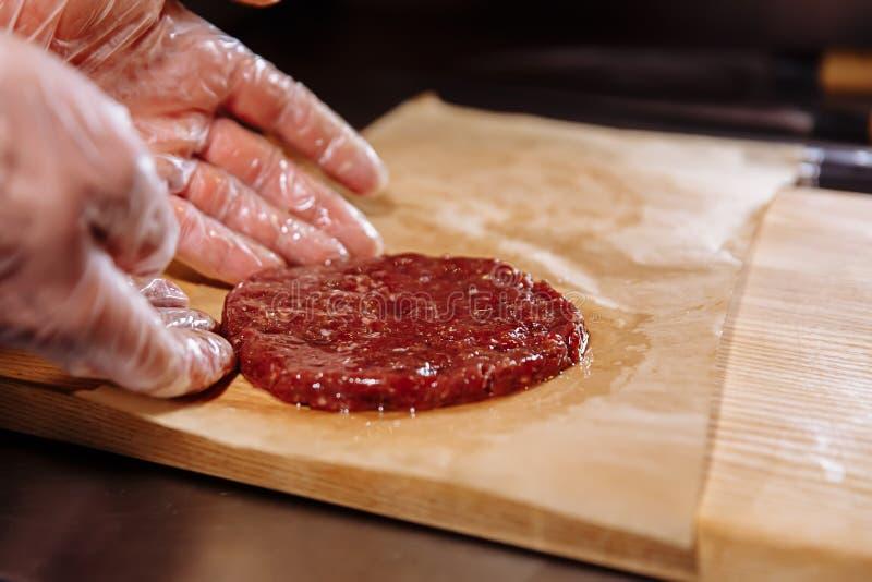 Cocinero que hace la hamburguesa El cocinero en guantes de la comida hace la chuleta Las chuletas se nivelan en el anillo de acer foto de archivo libre de regalías