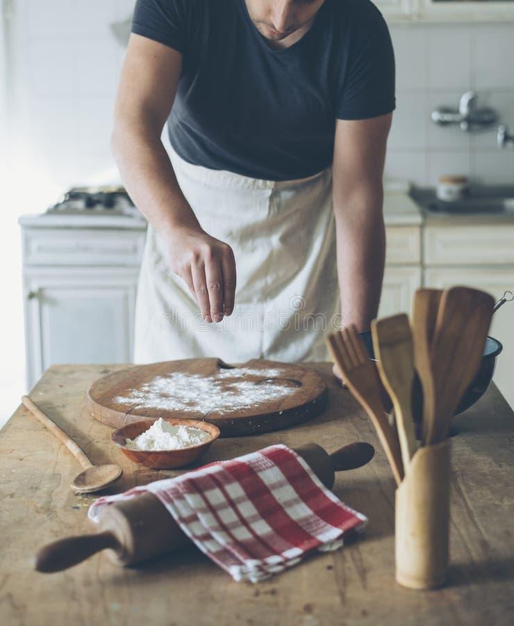 Cocinero que hace los pasteles en la tabla de cocina fotografía de archivo libre de regalías