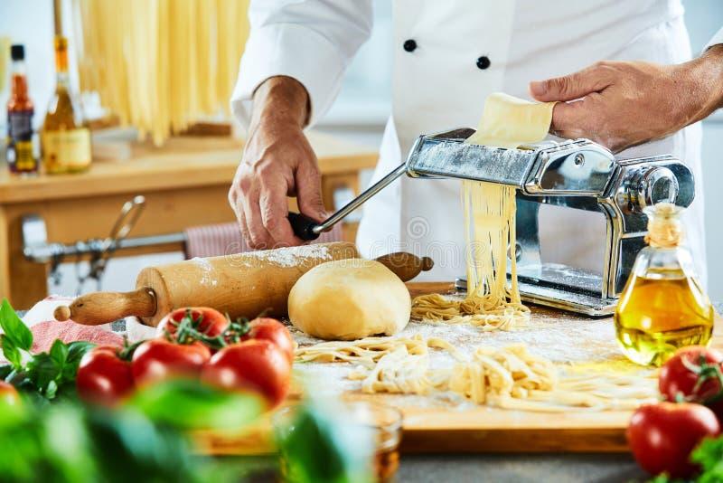 Cocinero que hace los tallarines con la cocina en fondo imágenes de archivo libres de regalías