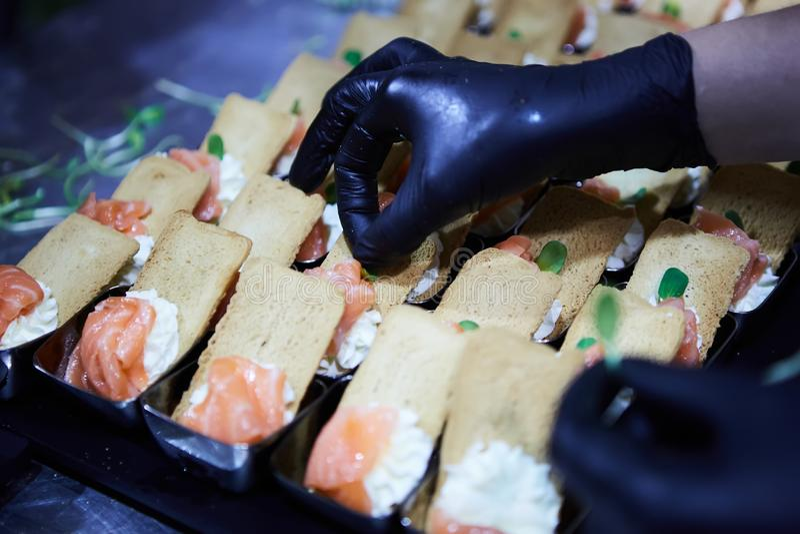 Cocinero que hace a Salmon Canapes fumado noruego con el queso cremoso imagen de archivo