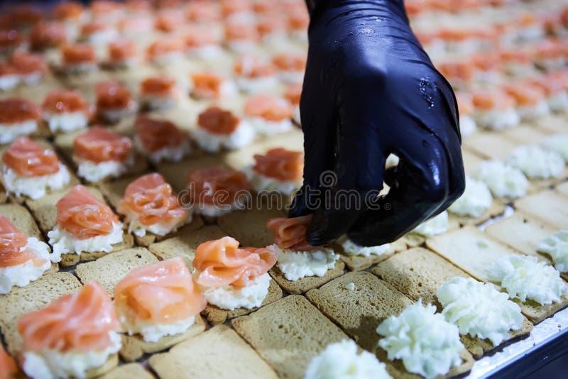 Cocinero que hace a Salmon Canapes fumado noruego con el queso cremoso imágenes de archivo libres de regalías