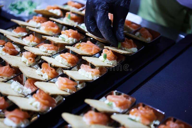 Cocinero que hace a Salmon Canapes fumado noruego con el queso cremoso fotografía de archivo