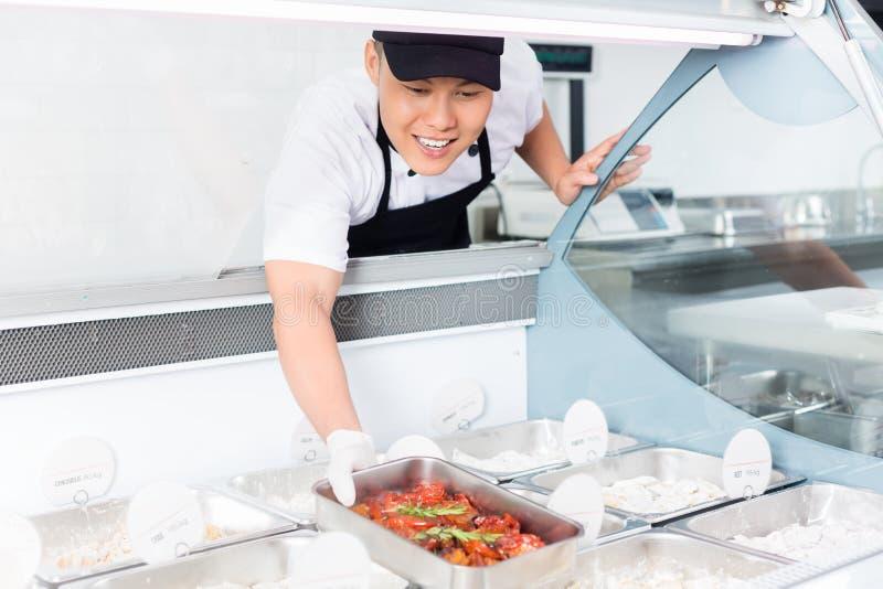 Cocinero que llena una bandeja de comida en una exhibición fotografía de archivo libre de regalías