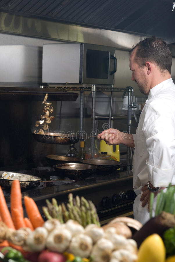 Cocinero que mueve de un tirón setas fotografía de archivo