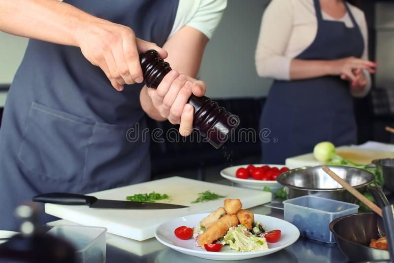 Cocinero que prepara la carne frita con la ensalada para servir en cocina del restaurante imágenes de archivo libres de regalías