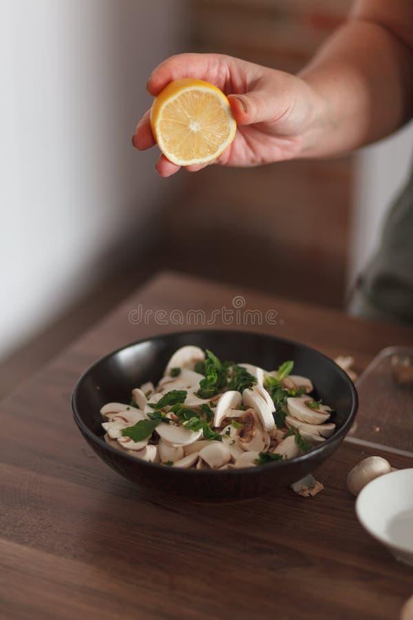 Cocinero que prepara la ensalada con las setas y la hierba foto de archivo