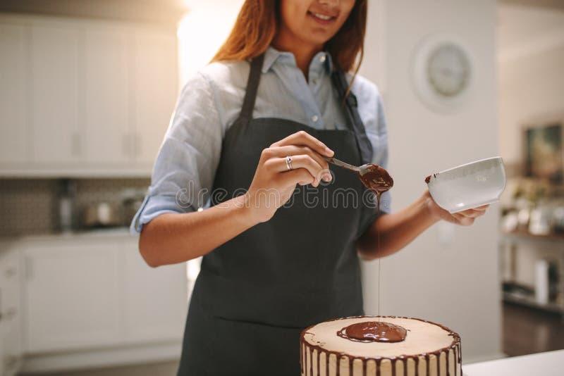 Cocinero que prepara la torta de chocolate sabrosa foto de archivo
