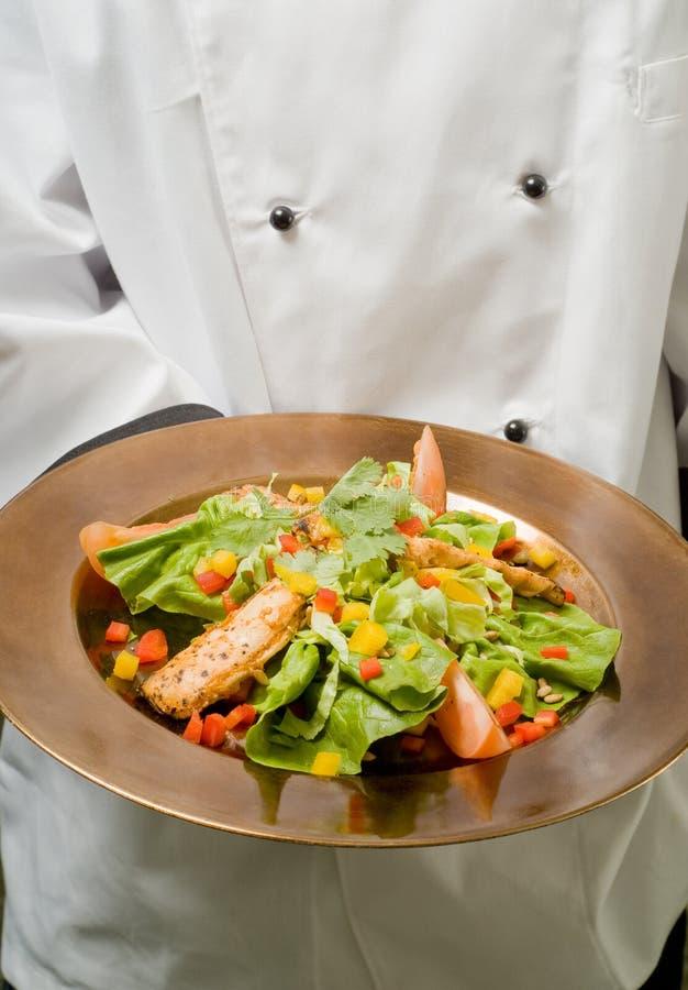 Cocinero que presenta la ensalada de pollo sana fotografía de archivo
