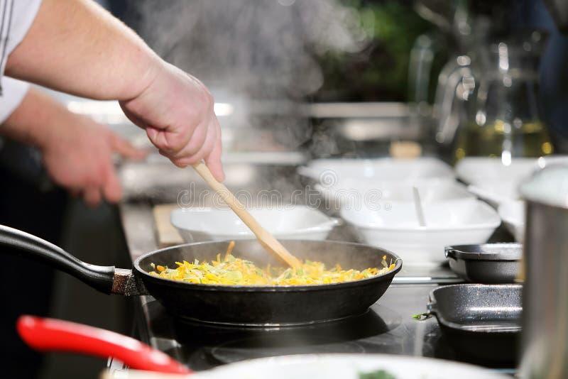 Cocinero que revuelve la comida en una cacerola imagen de archivo